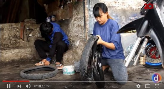 Irma Tri Resmiati, saat Memperbaiki Ban Sepeda Motor Pelanggannya yang Bocor